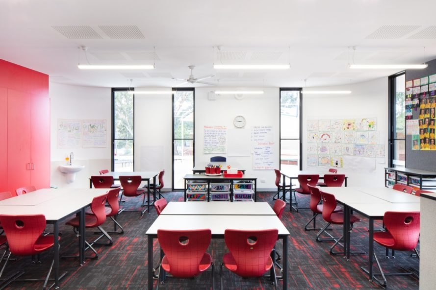 classroom with white desks and red chairs