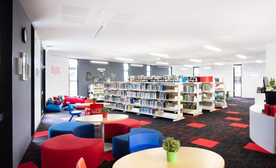library with racks of books and colorful seats