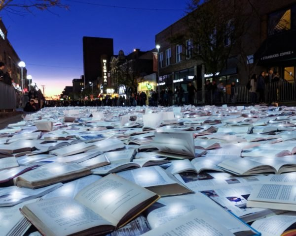 hundred of open books fill a street during the evening