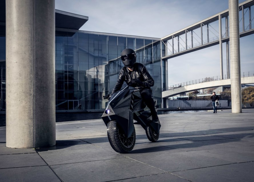 person siting on black NERA e-motorcycle in industrial complex