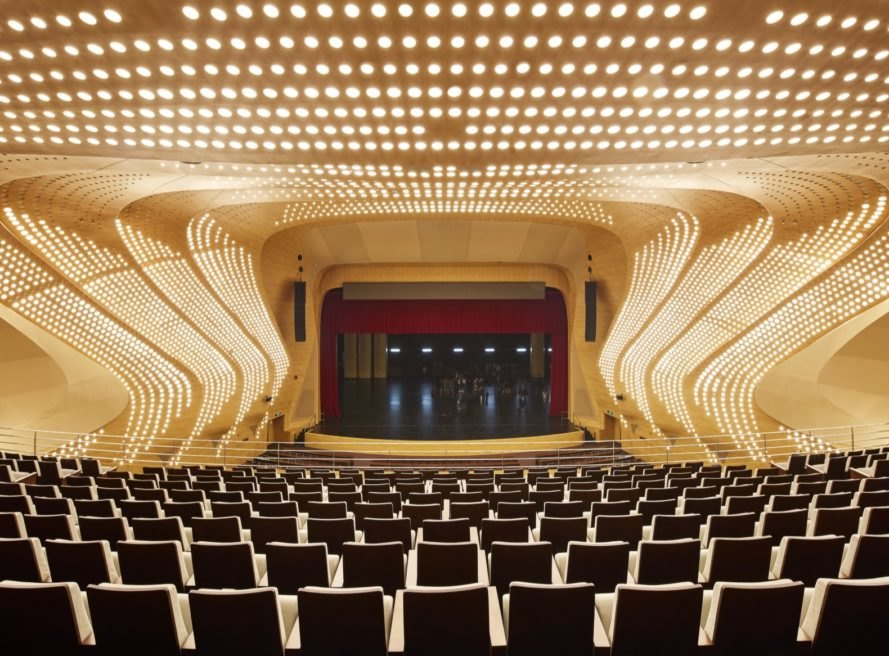 golden hued auditorium with rows of seats
