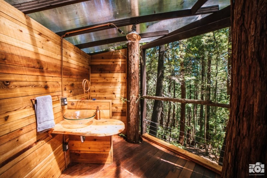 wood clad treehouse bathroom with large window