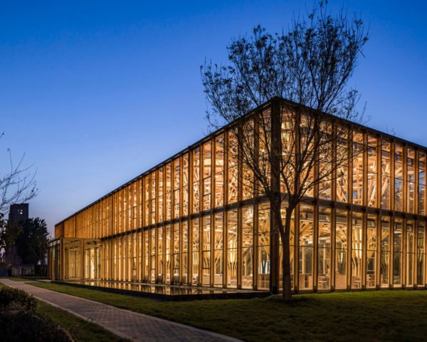 glass building with timber structures revealed on the inside