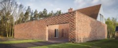 square brick home in a forest