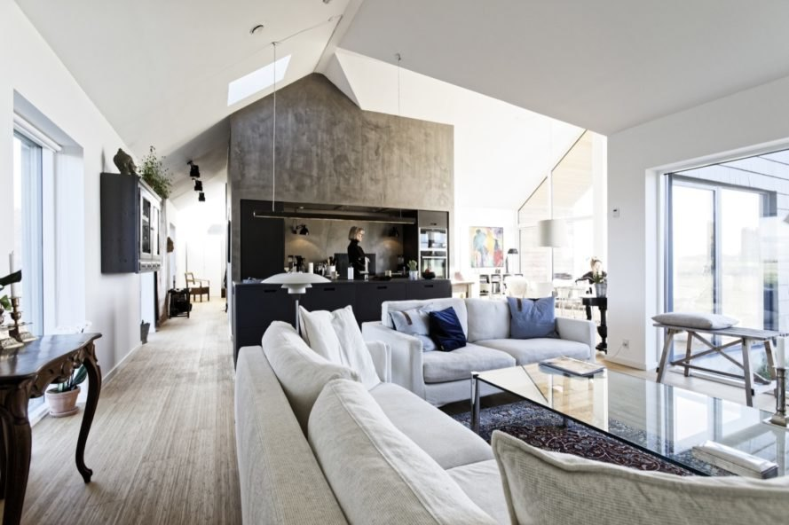 white interior with white couches, black kitchen and pitched ceiling