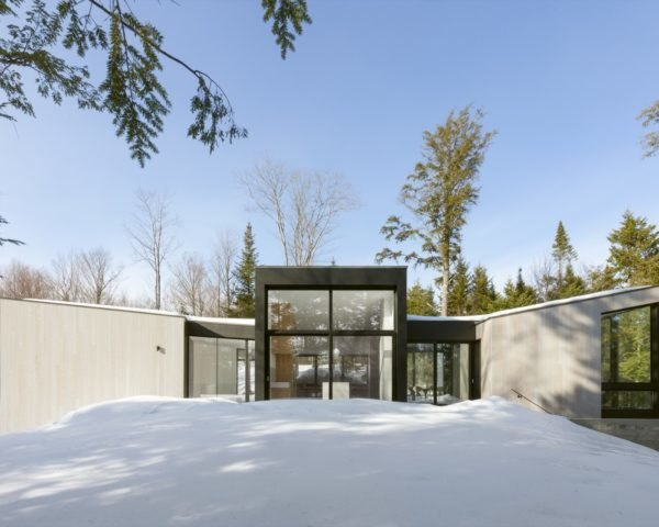 minimalist home with large windows surrounded by snow and trees