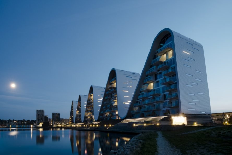 five curved, wave-shaped towers at night