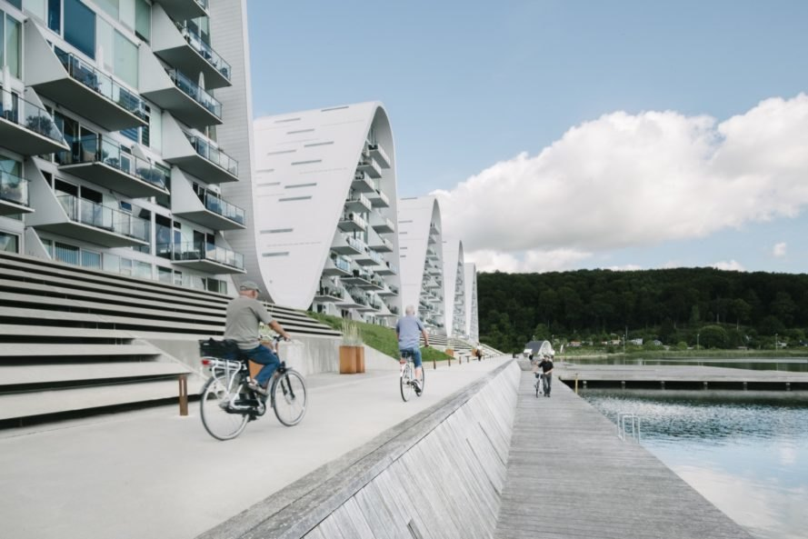 people riding bikes on the pier in front of wave-shaped buildings