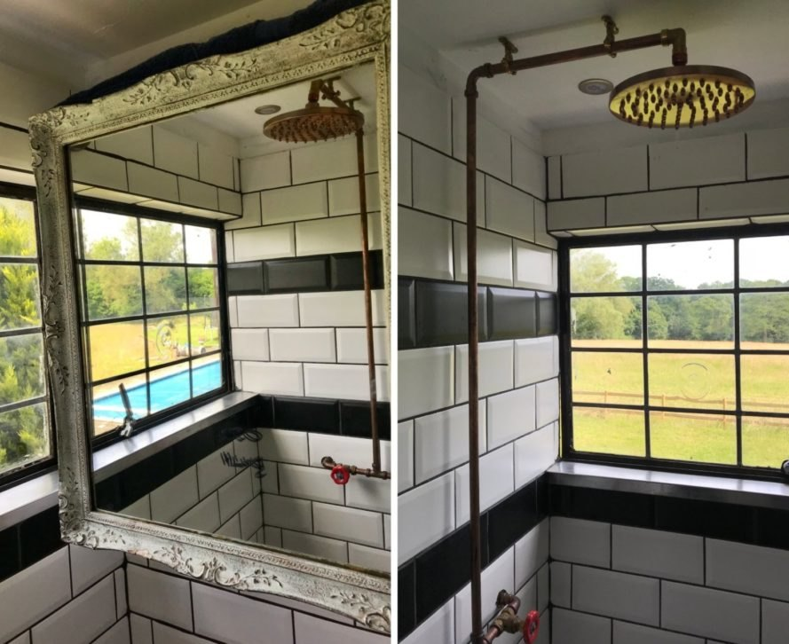 bathroom with subway tile and large mirror