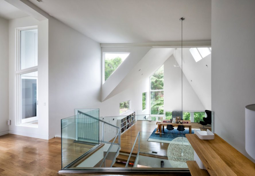 living space with angular ceilings and multiple windows