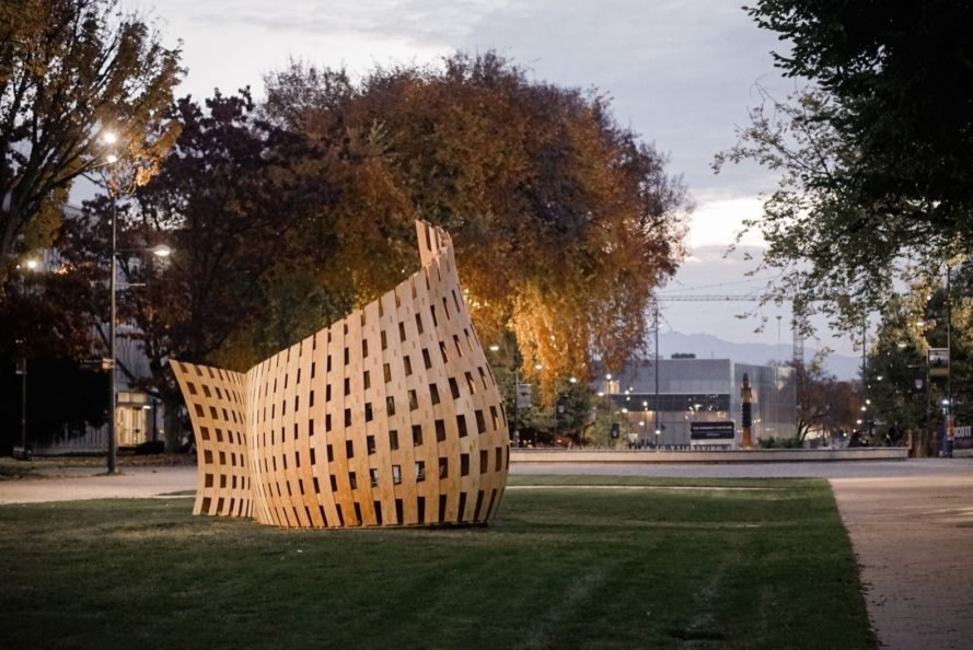 curved wood pavilion on grassy lot