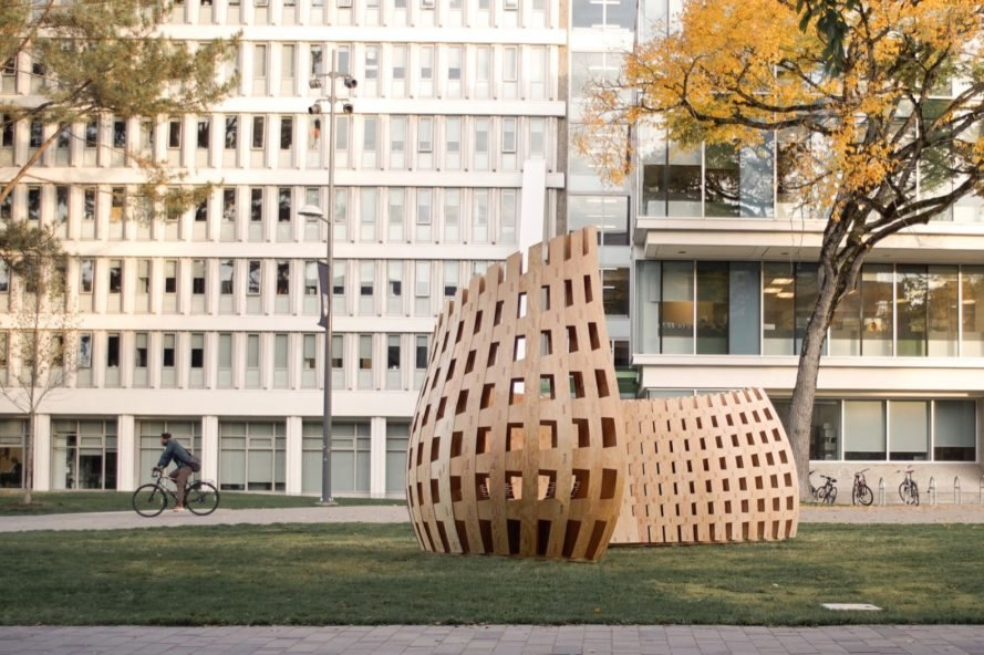 curved wood pavilion in front of a college building