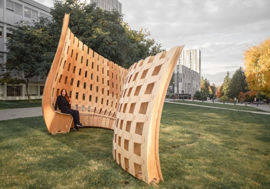 person sitting on curvy wood structure