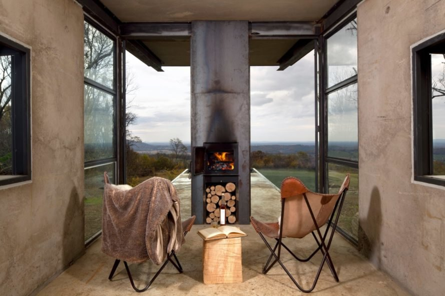 two chairs facing a fireplace with glass facade in the background