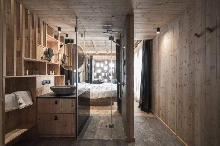 wood lined room interior of chalet with glass shower space