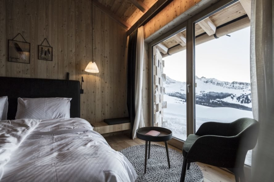 bedroom with large windows with snow covered mountains