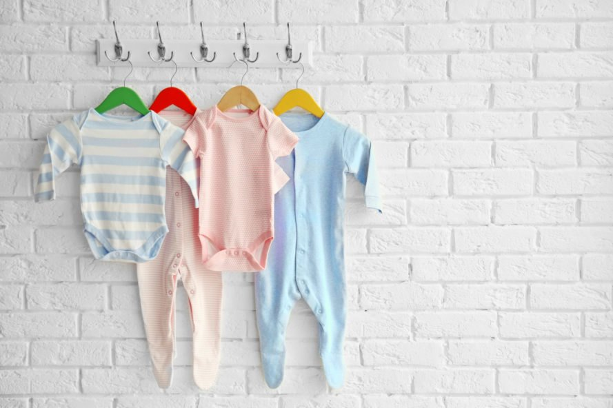 colorful baby clothes hanging on hooks on a white wall