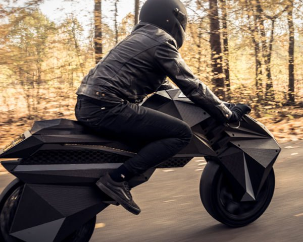 person riding black NERA e-motorcycle on road