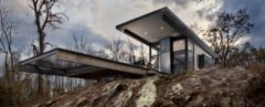 two flat roofs of a cabin jutting out over a rocky ledge