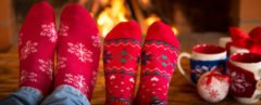 two pairs of feet in red socks near fire with mugs and gifts to the side