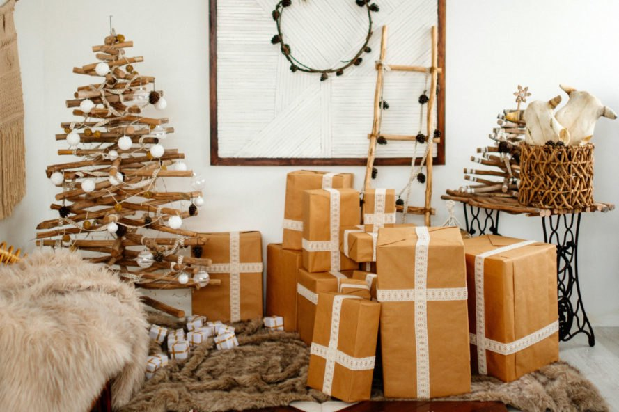 gifts in brown wrapping paper beside a minimalist all-wood tree