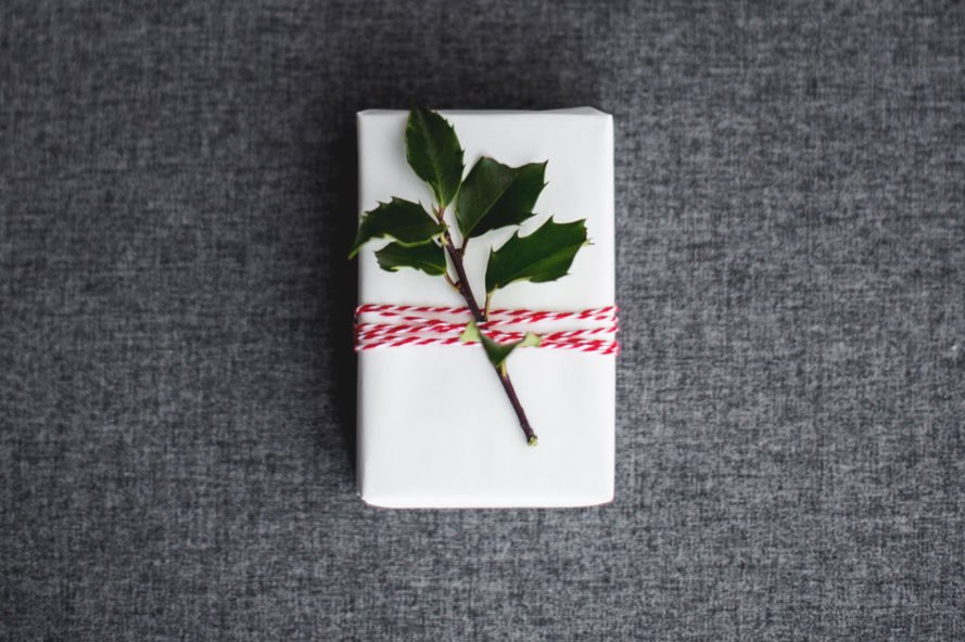white box wrapped in twine with leafy plant