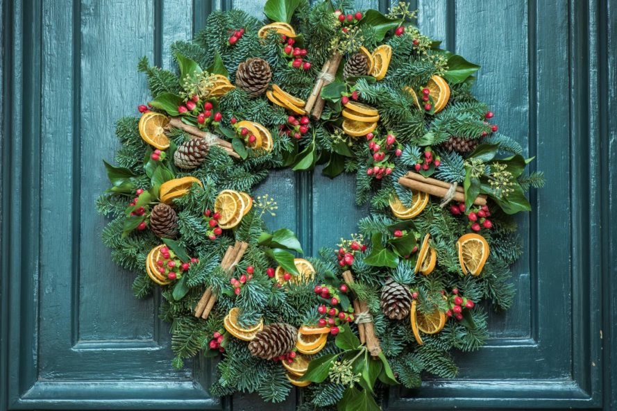 green wreath with pinecones and dried fruit on a green door