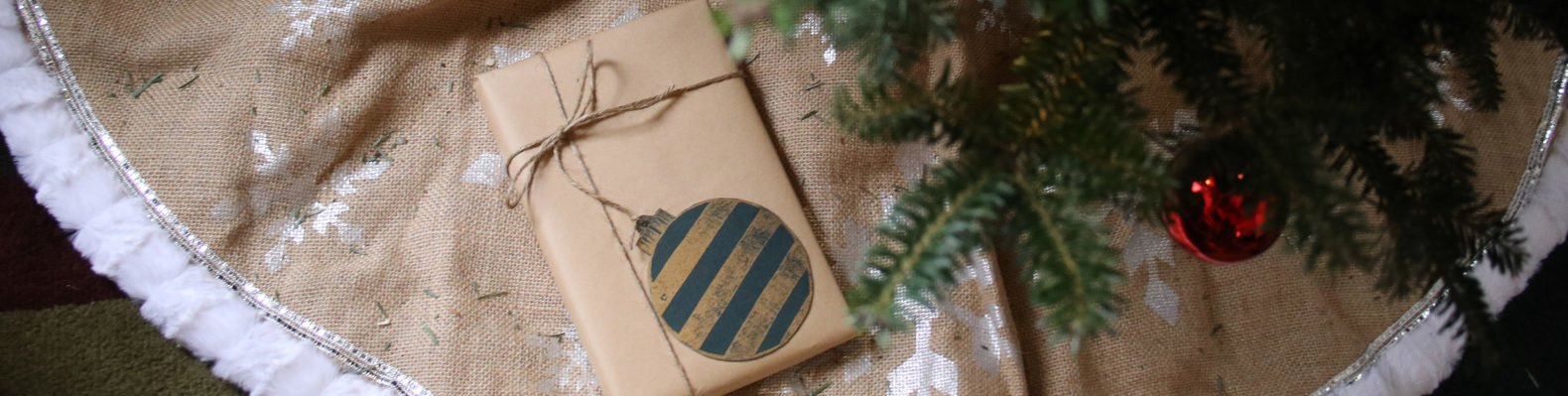 brown paper-wrapped gift under a green tree