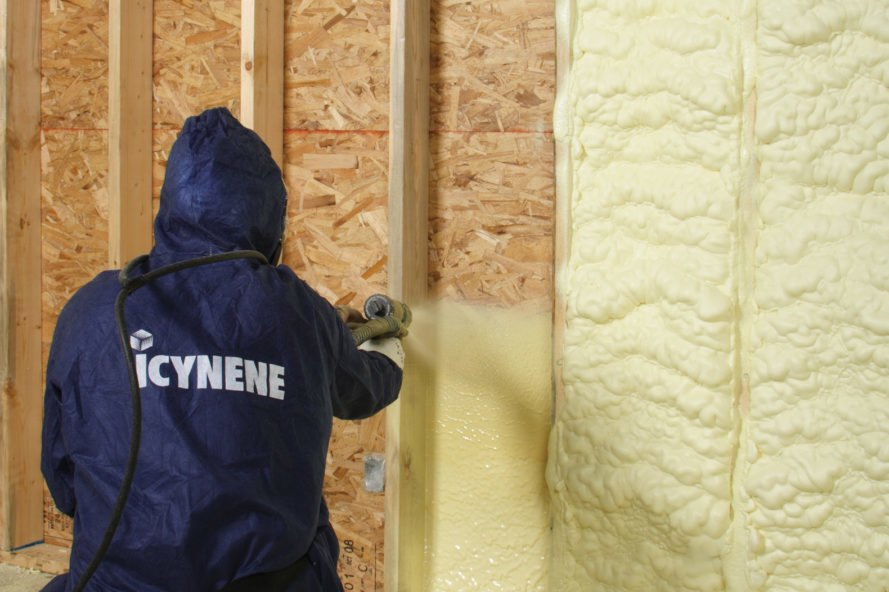 person spraying foam insulation into wood walls