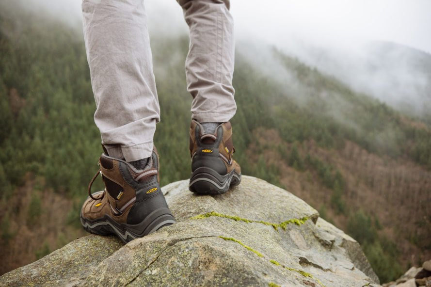 close-up of person wearing boots standing on a rock