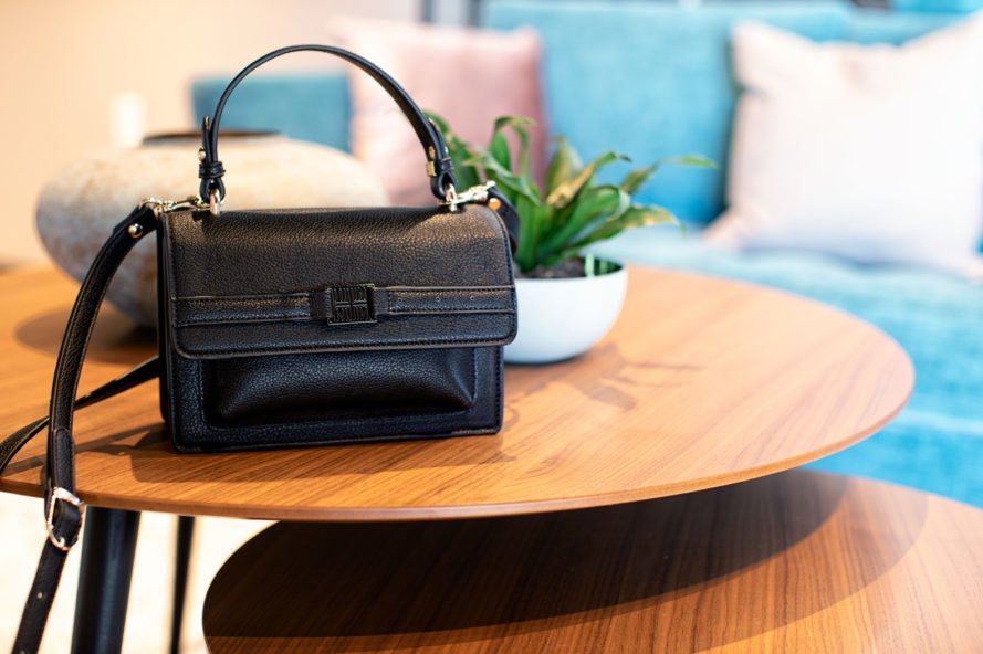 black vegan leather purse on wood coffee table