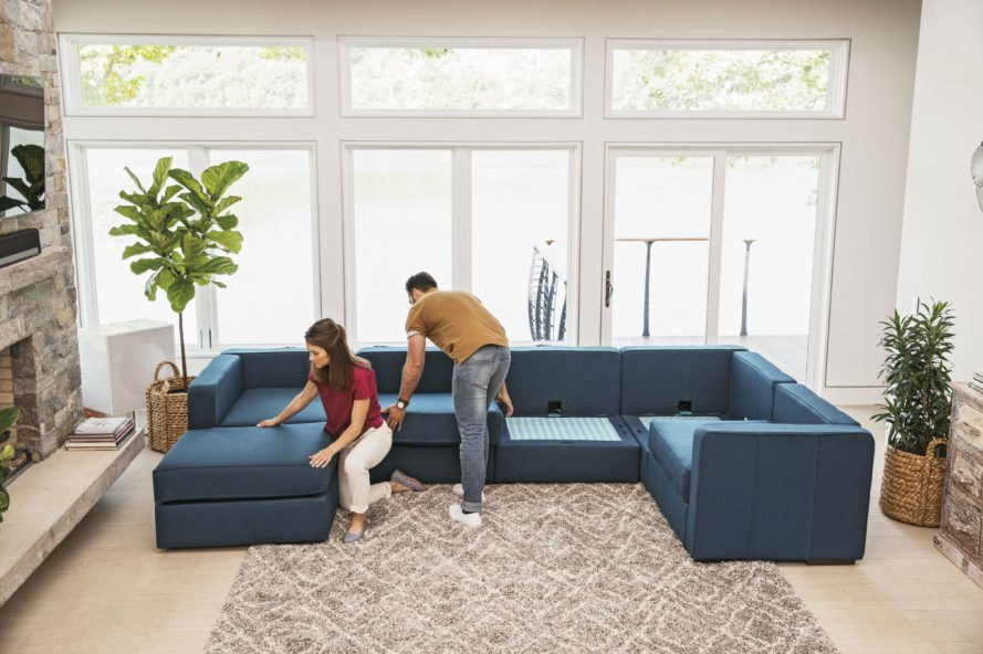 two people arranging a blue sectional sofa