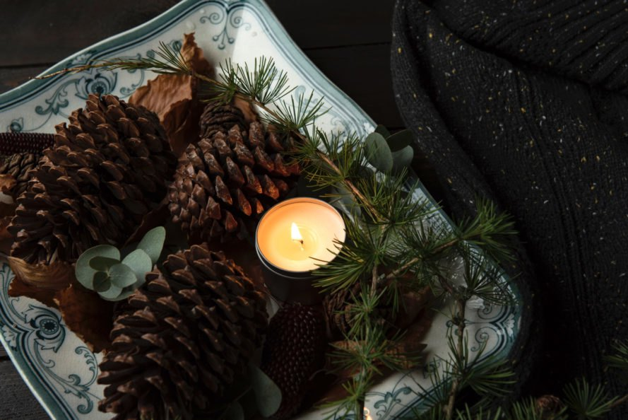 candle in tin container near pinecones