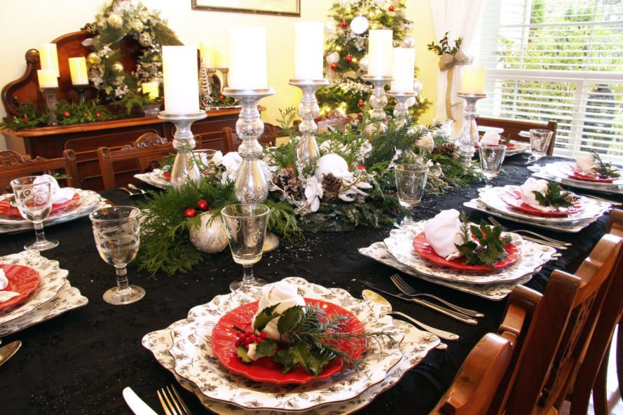 dinner table with centerpiece of candles and evergreen branches