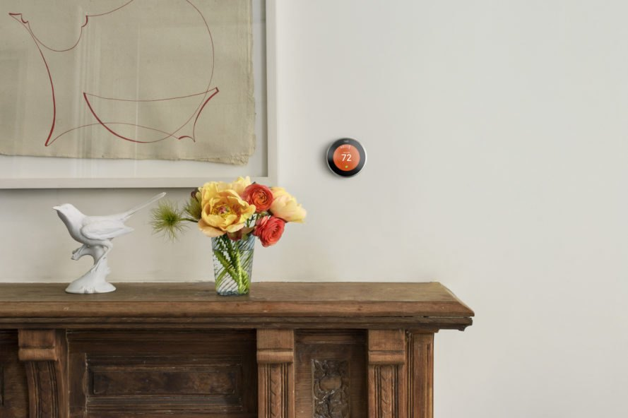 Nest smart thermostat on a wall beside a painting
