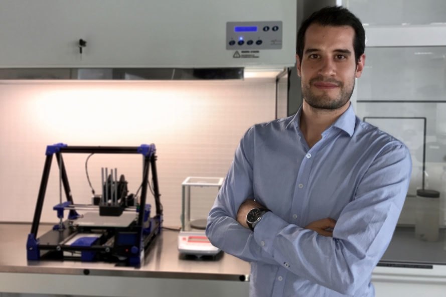 man with arms crossed standing in front of 3D printer