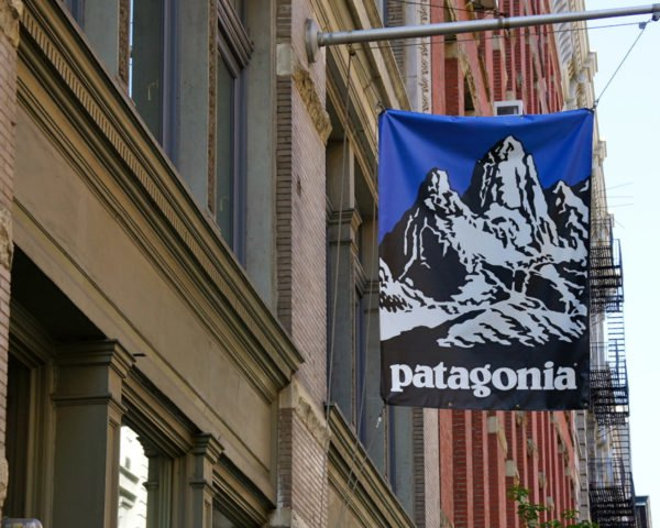 blue Patagonia store sign attached to old brick buildiing