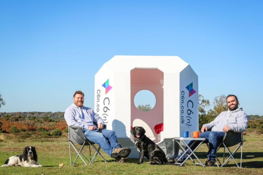 two people and dog sitting in lawn chairs outside a small white pod