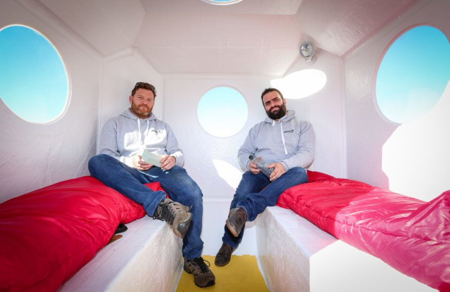 two people sitting inside a small white pod