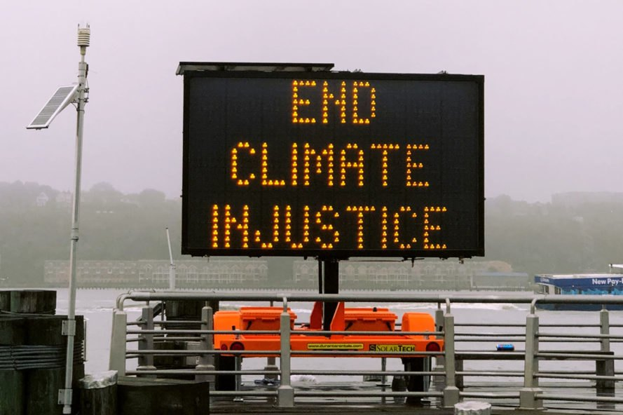 "traffic sign reads ""End Climate Injustice"""