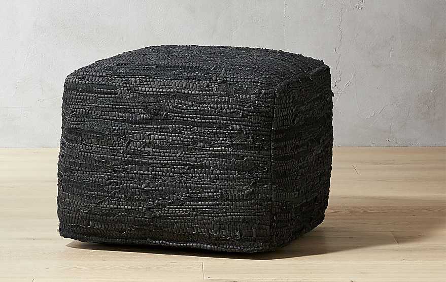 black pouf seat on wooden floor