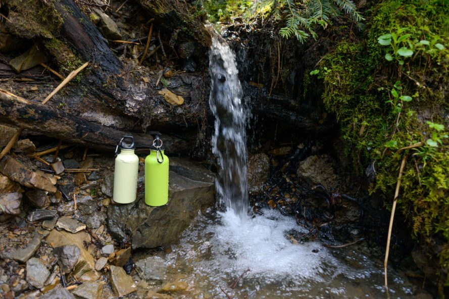 two reusable water bottles on a rock in front of a waterfall