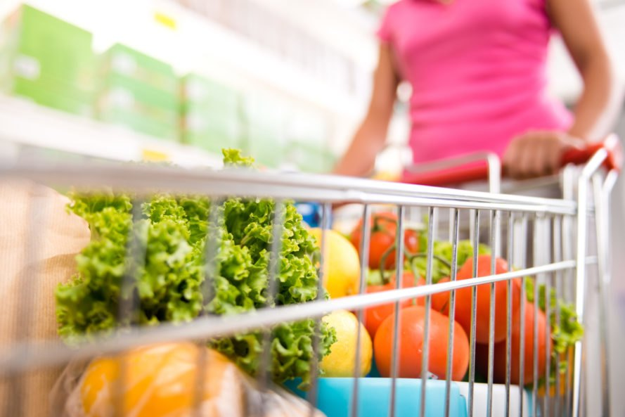 woman pushing grocery cart with vegetables and fruits