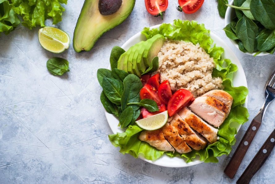 bowl of chicken with greens and grains with tomatoes and avocado