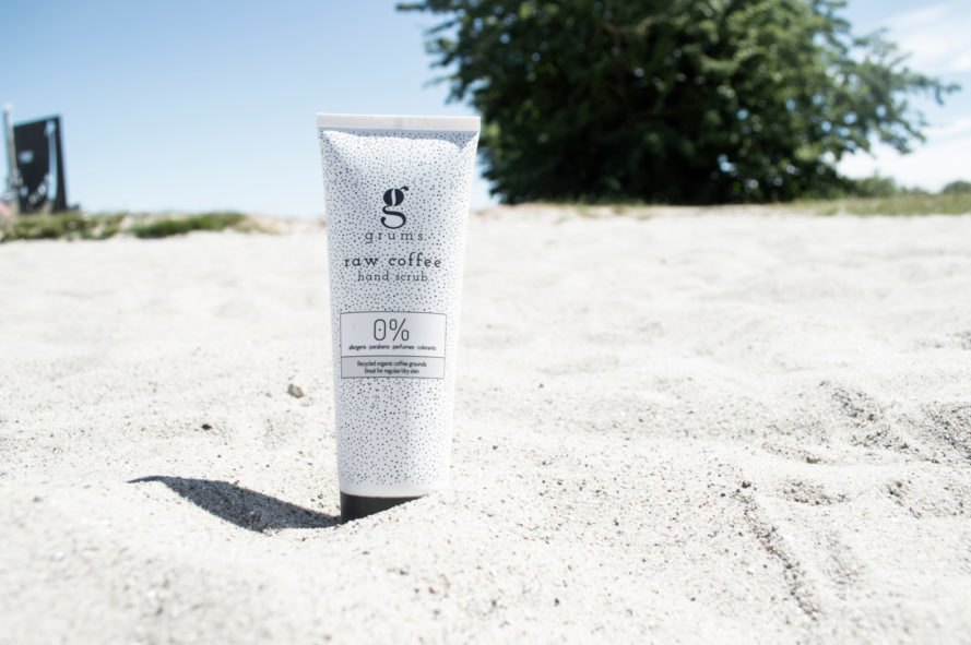 white skincare bottle in the sand