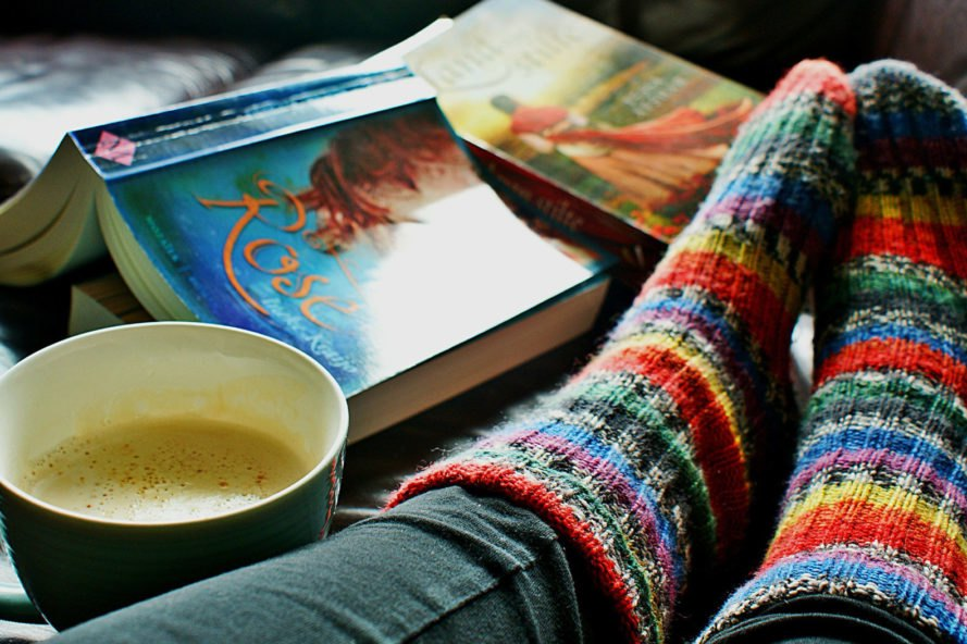 person wearing rainbow knit socks with a cup of coffee and books near feet