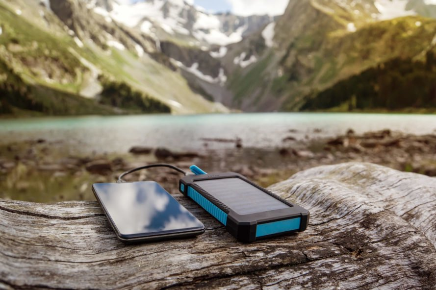 phone and solar-powered phone charger on a log with mountains in background