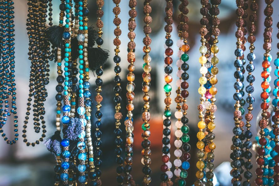 colorful beaded necklaces hanging from display
