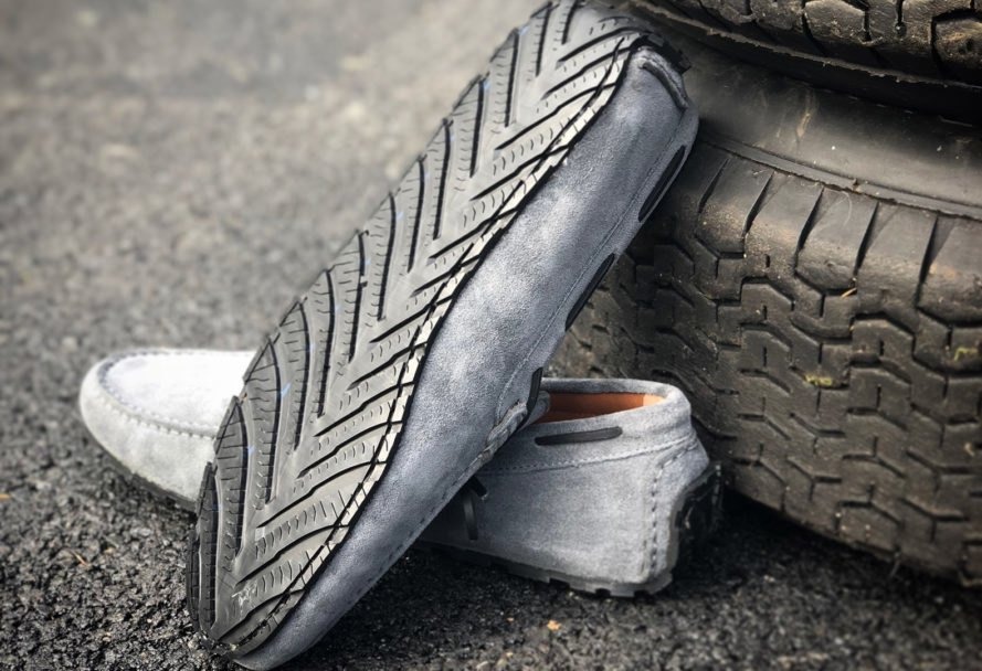 gray loafers propped up against car tires