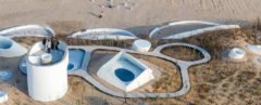 curvy white buildings and walkway embedded into dune landscape